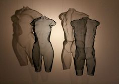 CYNT and CYNW 2016 with shadow projections - Wire Art! Female and male body torso in black painted steel-mesh, Suspended sculpture, height 64cm each. Contemporary art by sculptor David Begbie.