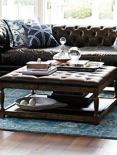 Generously padded and deeply button-tufted, the cocoa-colored Lucerne Tufted Leather Ottoman is a rich addition to your seating space and serves as a handsome place to display design accessories or as additional seating. Tufted Leather Ottoman, Leather Ottoman Coffee Table, Footstool Coffee Table, Leather Footstool, Oversized Chair And Ottoman, Coffee Tables, Coffee Table Design, Cool Chairs, Wooden Shelves