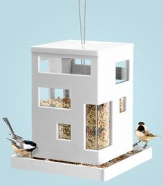Invite wild birds to dine in style-and satisfy your taste for modern design-with this hip new spin on the traditional bird feeder. The Bird Cafe bird feeder from Umbra features a cube-shaped architectural form with asymmetrical windows and a sleek, white finish. - $26.69