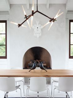 Barbara Hill designed this modern home in Atlanta, Georgia. Its informal dining space has a slightly rustic feel, sporting bronze and wood in the form of a Lindsey Adams Adelman chandelier for Roll & Hill and a table by Terry Dwan, mixed with folk-art touches like the Eames House Birds and a cuckoo clock from Diamantini & Domeniconi. The PK8 chairs from Republic of Fritz Hansen were designed by Poul Kjærlholm and sourced from Kuhl-Linscomb in Houston, Texas.