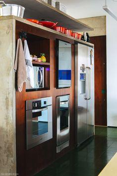 Cozinha integrada conta com estrutura dos móveis feita em concreto e acabamento em marcenaria.