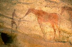 Tarssed Jebest, Algeria. Faded red standing man holding reins of faded red horse facing left. #africanrockart http://africanrockart.org