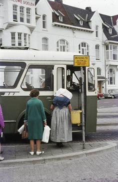 Vrouw in protestantse Zuid-Bevelandse streekdracht bij een bushalte te Middelburg. 1969- Loskade