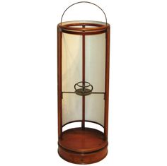 Taisho period (1920s) Japanese andon (rice paper lantern). The amount of illumination can be controlled by sliding the rounded rice paper panel. Bronze candleholder is in the interior center with a small drawer to hold matches at the base of the lantern.