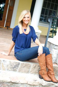 """This navy blue top is a great addition to your fall wardrobe! It's accessorized with gold accent buttons on the sleeves and features a high-low bottom. (Fits true to size)  The boots pictured are available too! Check them out under """"Jolene"""" Boots when you click on the """"All Products""""."""