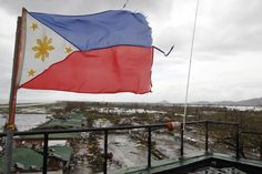 A Philippine flag flutters atop the control tower of a damaged airport after super Typhoon Haiyan battered Tacloban city | Super storm 'Yolanda' (Haiyan) hits the Philippines - Yahoo News Philippines