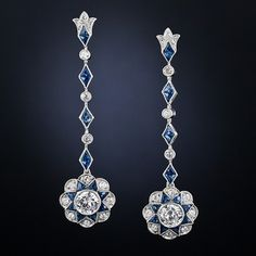 A pair of bright-white European-cut diamonds, together weighing three-quarters-of-a-carat, radiate from the centers of eight-pointed sapphire stars, which in turn, swing and sway below a line of alternating small round diamonds and diamond-shape sapphire sections, in these dazzlingly beautiful, 1 1/2 inch long drop earrings - crafted during the latter-twentieth century in consummate Art Deco style.