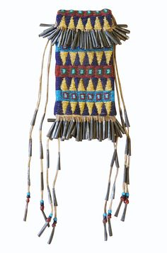 An extraordinary piece of Apache artwork, this Jicarilla man's beaded belt pouch was made in the 1880's. Collected by a rancher in the 1920's this piece represents a synthesis between traditional Apache design and the dominant Plains Indian cultural influences that make early Jicarilla bead work so wonderfully unique. Fringed with hundreds of tiny rolled tin cones this tightly beaded, sinew sewn bag is visually stunning because of its early color choices and the triangular/banded motif.
