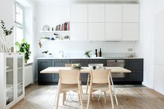 Des éléments de cuisine agencés sur un seul mur, complétés par des meubles indépendants, dans des tons clairs et une table de salle à manger en bois blanchi : un ensemble léger et lumineux