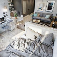 Die Einrichtung im Schlafbereich ist grau und wird durch Schränke vom Rest getrennt