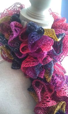 Hand knitted Ruffle Scarf in shades of Navy/Fuschia/Purple/Olive with a shimmery silver thread accent. MEMBER - Shore Thing Designs
