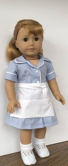 Maryellen loves this waitress uniform. Perfect for her to use in her diner ! The light blue dress is made from a cotton fabric. White trim is sewn to the front edge, collar, and hem of the sleeves. The dress has five white buttons down the front and closes with snaps sewn under