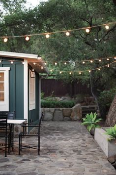 Backyard patio with lights - love the idea of using real  stones