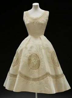 Pierre Balmain (1914–82) opened his couture house in 1945. He had previously trained alongside Christian Dior at the couture house of Lucien Lelong. This is one of his couture evening dresses 1950-1955 cream silk grosgrain with matching machine made Swiss embroidery edging the low round neck, banding the hem and forming roundels on the wide curving flaring skirt. Source: http://collections.vam.ac.uk/item/O120591/evening-dress-balmain/