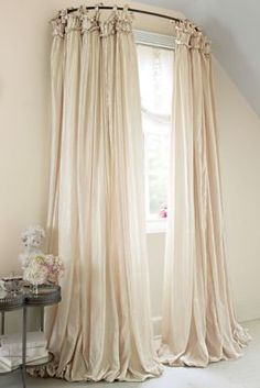 Use a curved shower curtain rod to make a window look bigger. It's called balloon drapery and it will make any living room look just GRAND.
