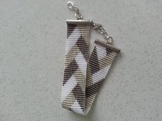 Très beau bracelet manchette, aspect contemporain, réalisé à la main avec des perles de rocailles Miyuki 15/1 (très fines) couleurs : gris, blanc et argent largeur du tissage : 2 cm longueur : 13,5 cm sans les attaches Dautres couleurs et taille sur demande