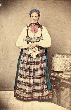 """67. (ant.) Jentedrakt/kvinnedrakt, Nes, Hallingdal. Portrett av jente/kvinne  stående i fotoatelier med nøytral bakgrunn og tregulv, med kiste og stor sveipet eske(?) ved siden av henne.  Fra serien """"Norske Nationaldragter"""" (ant. nr. 67), fotografert av Marcus Selmer (1819-1900), Bergen."""