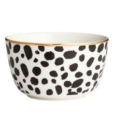 Weiß/Schwarz. Porzellanschale mit aufgedrucktem Leopardenmuster, goldfarbenem Rand und schimmerndem Textdruck auf der Innenseite. Höhe 7,5 cm, Durchmesser
