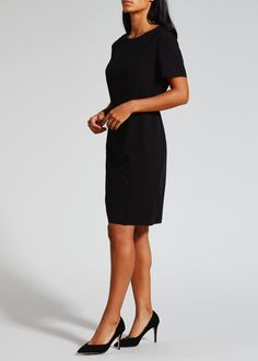 Short sleeve shift dress in black made with stretch fabric. Featuring a back zip fastening with a vent for a more comfortable fit and piping detail at the...