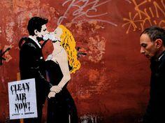 """Marcello Mastroianni et Anita Ekberg contraints de s'embrasser avec un masque antipollution, sur un graffiti de TVBoy photographié le 14 novembre à Rome. L'artiste de rue a réalisé plusieurs œuvres dans la capitale italienne dans le cadre de la campagne de Greenpeace """"Clean Air Now"""" contre la pollution de l'air.    AFP PHOTO / Alberto PIZZOLI"""