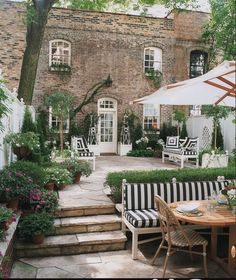 Stone patio. Stone stairs. Striped furniture. Manicured but rough landscaping.