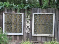 Old diamond shape leaded glass windows..hanging on fence..I can envision a nice sitting area nearby...  great way to dress up a boring fence