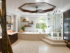 Dark wood vanities and white textured walls give this bathroom a crisp, refreshing feeling. A tray ceiling calls attention to a woven ceiling fan, while a frameless glass shower is inconspicuous in the corner.