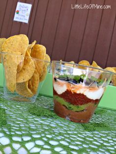 Simple seven layer dip for bite size snacking!    Assembly:    Prepare refried beans. Add taco seasoning to flavor the beans, if desired. Allow to cool, then scoop the beans into a ziplock bag. Snip off a small corner of the bag and pipe the beans into the bottom of the cups.  Place the guacamole, salsa, and sour cream all in separate ziplock bags.