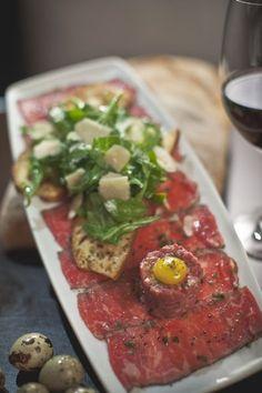 Our BEEF CARPACCIO: Steak Tartare, Quail Egg, Ciabatta Toast, Shaved Parmesan Cheese.