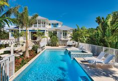 A twist on tradition, this stunning Captiva Island home's formal entrance overlooks the swimming pool. Elevated about six feet above grade and anchored to a poured concrete piling foundation, the pool is lined with all-weather wicker chaise lounges from Summer Classics.