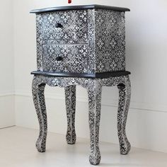 A gorgeous bedside or side table, crafted from wood then fully encompassed in embossed metal sheeting to create a wonderfully ethnic, pretty finish.This black embossed sheeting begins life as shiny silver before being coated in thick black paint which fills in the gaps, creating a fantastic decorative contrast pattern. The blackened version features complementary rounded black knobs and trim. Whereas the silver version is bright and showy, the blackened version is toned down because half the ...