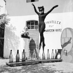 """17 year old Bianca Passarge of Hamburg dresses up as a cat, complete with furry tail, and dances on wine bottles, June 1958.  Her performance was based on a dream and she practiced for eight hours every day in order to perfect her dance."""