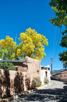 Adobe buildings, an impossibly blue sky and turning fall leaves in Taos, New Mexico. Via Thought & Sight travel blog.