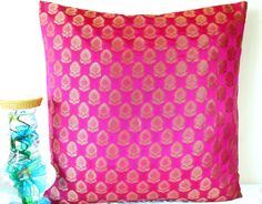 The pillow cover is made with Dark Pink premium Indian Silk Brocade fabric. Dull gold shimmer woven floral motifs adorn the rich pink background,