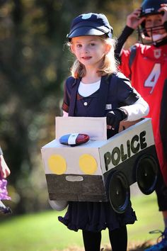 Store bought police girl costume and car made from hammermill paper box, cut and painted; wheels bolted on from paper plates and a bicycle police light and siren purchased from Amazon. Huge hit, and lots of fun for her to wear.