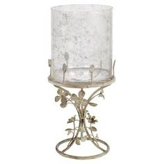 """Lend a touch of timeless appeal to your console table or mantel with this lovely candleholder, showcasing a scrolling metal frame and charming floral accents.  Product: CandleholderConstruction Material: Metal and glassColor: TanFeatures:  Scrolling frameFloral accentsDimensions: 19.5"""" H x 9"""" W x 9"""" DCleaning and Care: Wipe with damp cloth"""