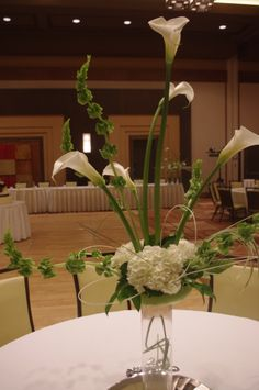 High Style! Beautiful & memorable wedding centerpiece! Calla Lilies, White Hydrangea, Bells of Ireland, Fat Jay Leaves, Bells of Ireland accented with white milano sticks
