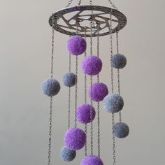 Mobile made out of an old bicycle brake disc and handmade acrylic pompoms .