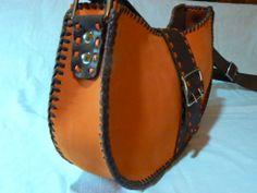 Bolso de color naranja y marrón, todo realizado en piel y cosido a mano,