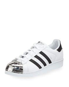 """adidas leather low-top sneaker with striped sides. 1"""" flat heel. Metal round toe. Lace-up front. Logo-embossed heel counter. Padded footbed. Rubber outsole. """"Superstar"""" is imported."""