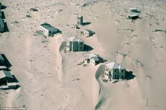 Sand dunes surround the abandoned houses of the ghost town of Kolmonskop, Namibia