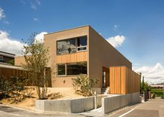 An elevated cedar terrace stretches along one side of this narrow house in Nara, Japan, providing the residents with glimpses into the neighborhood. The slender rectilinear volume by Kobe architect Keiichi Sugiyama measures five by 17 metres and is covered in a combination of cedar wood and muted brown render.  Two bedrooms join the living space at ground level, while the master suite and a study are set on the first floor. A garage is wedged beneath the living space.