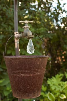 Garden Art, faucet with crystal water drop and rusty bucket.