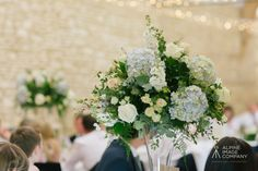 Tall glass flute vase table centres in Wenman's Barn at Caswell House #joannacarterflowers #caswellhouseweddingflowers #oxfordshireweddingflowers