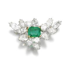 Emerald and diamond brooch Of spray design, set with a step-cut emerald and brilliant-cut, pear- and marquise-shaped diamonds.