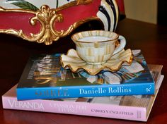 A favorite way to enjoy a cup of tea- in a MacKenzie-Childs Parchment Check teacup and leafing through pretty design books