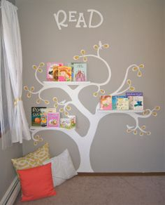 Reading nook using wall sticker and shelves.  Gutter shelves or spice racks would work perfectly.
