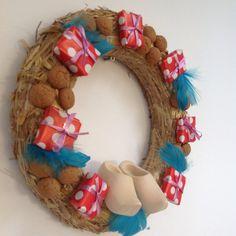 Sinterklaas decoratie met krans van action, houten klompjes, pepernoten en kadootjes met piepschuimvulling.