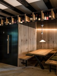all interior finishings, u-shaped benches in oak, wine room waxed in black steel including wine racks, niches