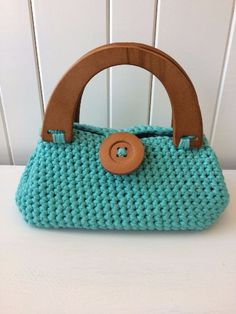 This handmade teal crochet purse is absolutely adorable! The top handle bag features sturdy fashionable wooden handles in a wood finish. With a top loop closure, the front is adorned with a large wood